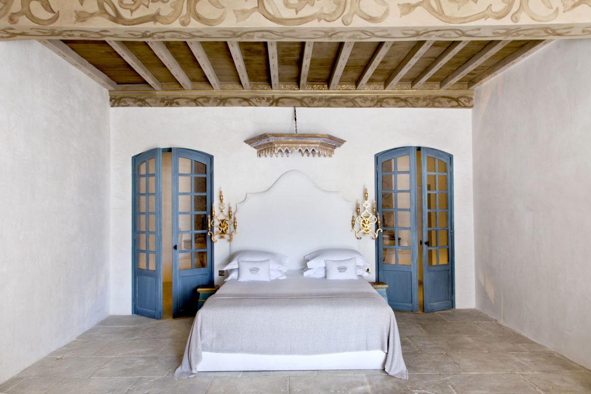 Chambre avec ciel de lit d'antiquaire et appliques façon candélabres.